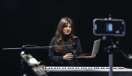 Girl musician with laptop, recording video on smartphone standing on tripod, using professional microphone, blogger or music teacher shooting course in studio, sitting at the piano. Banque d'images