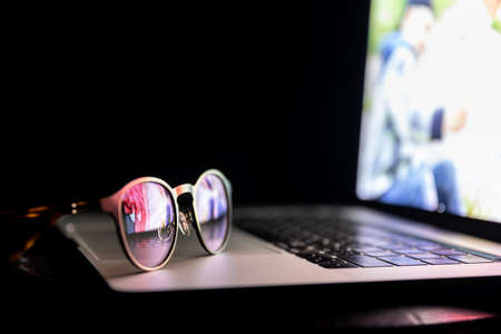 Glasses lie on the laptop, reflecting light from the screen in the dark, copy space. Banque d'images