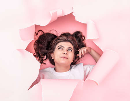 Attractive brunette girl peeking out from a hole in the paper on a pink paper background, top view.