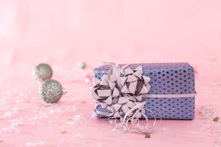 Close-up of a Christmas present on a blurred pink background with Christmas toys, copy space.