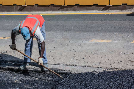 Road Worker Raking Asphalt photo