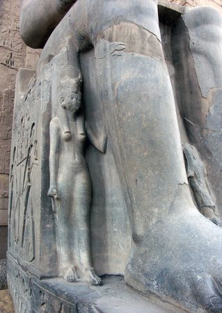 Statue of a wife or a daughter of Ramses The Great at the feet of his larger statue