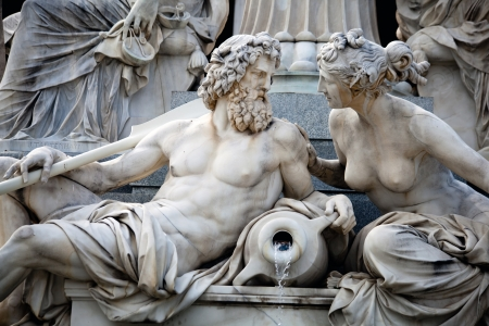 A male and a female statues in the Athena Fountain  Pallas-Athene-Brun nen  situated in front of the building of Austrian Parliament   photo