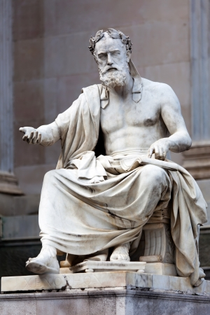Statue of a philosopher in the ancient Greek style, situated in front of the building of Austrian Parliament   photo