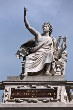 Statue of Orpheus holding a lyre in an ancient Greek style on top of a building in Vienna   photo