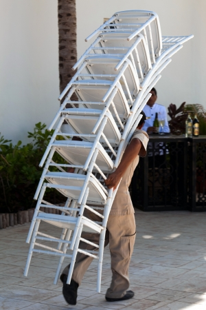 Hotel worker carrying a stack of chairs