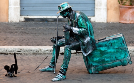The term living statue refers to a mime artist who poses like a statue or mannequin, usually with realistic statue-like makeup, sometimes for hours at a time.