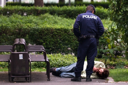 Vienna policeman inspecting a man laying on the ground