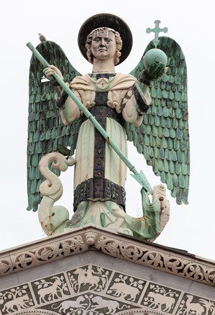 lucca: The 4 m-tall statue of St. Michael the Archangel on top of the San Michele in Foro, the Roman Catholic basilica church in Lucca, Tuscany, central Italy