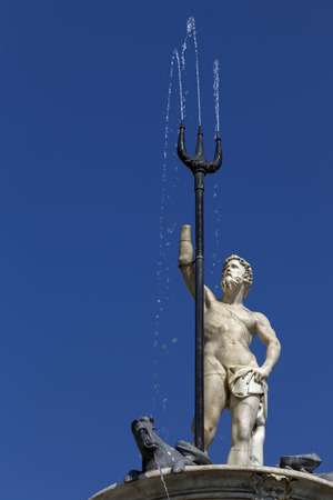 nymphs: The Fountain of Neptune in Naples, Italy was built by Giovanni Domenico DAuria in 1601. In the center two nymphs and two satyrs hold up a saucer that features a statue of Neptune with trident. Stock Photo