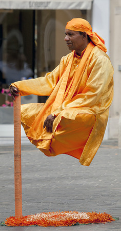 ROME, ITALY - AUGUST 1 2015: One explanation of the secret behind the levitating yogi is that the pole is attached to a camouflaged stable metal platform, that can support the weight of the performer. 新闻类图片