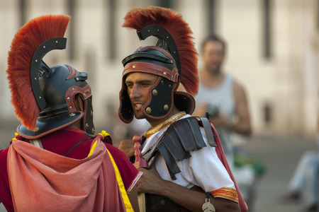 enactment: ROME, ITALY - JULY 29 2015: Men dressed up as a Roman legionnaires are a frequent sight on the streets of Rome, Italy. They are making money mostly by posing for pictures with tourists. Editorial