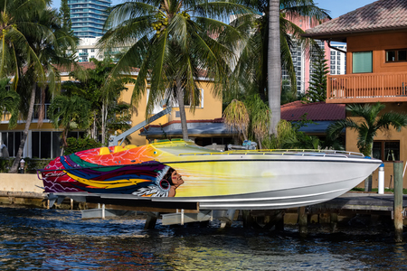 isles: SUNNY ISLES BEACH, FL - JANUARY 1 2016: Speedboat in front of the luxury villa in the Sunny Isles Beach, located on a barrier island in northeast Miami-Dade County, Florida.