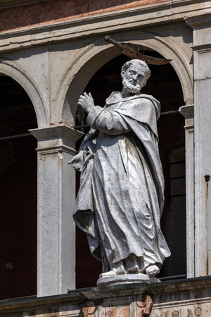 saint peter: Medieval statue of Saint Peter the Martyr with a hatchet in his head decorating the facade of the Cremona Cathedral.