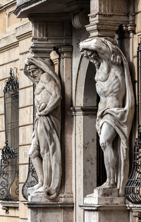 telamon: Statues of Hercules at the entrance to the 18th century Palazzo Vescovile (Bishops Palace) in the historical center of Mantua, Italy Stock Photo