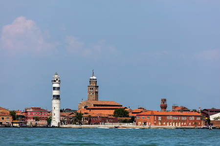 Murano: MURANO, ITALY - APRIL 30 2016: Faro di Murano Lighthouse on the Venetian island of Murano, a round cylindrical stone tower with three black horizontal bars near the top, built in 1912. Editorial