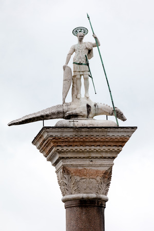 12th century column with the statue of Saint Theodore, the patron of Venice before St Mark, holding a spear and standing above a crocodile, that represents a slain dragon.