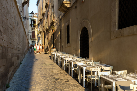 ortigia: SYRACUSE, ITALY - AUGUST 15 2016: The streets of the island of Ortigia, the historical heart of Syracuse, are lined with restaurants and offer many options for fine dining.