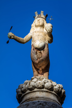 scepter: The Taorminas emblem, two-legged centaur wearing a crown and hoisting a scepter in the right hand and a globe in the left, set on top of the Baroque  fountain built in 1635.