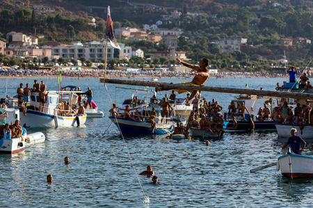 supposed: CEFALU, ITALY - AUGUST 20 2016: Tinna at sea game in Cefalu where the winner is supposed to grab the flag bearing the image of San Salvatore, hanging on the end of a pole lathered with soap and fat Editorial