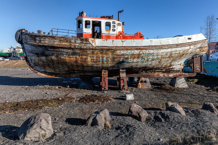 Old wooden boat on shore in the Reykjaviks harbor in Iceland.