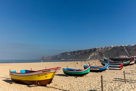 Praia da Nazarestrand in Nazare, Portugal. Historische voorbeelden van de kleurrijke vissersboten die de lokale vissers nog niet zo lang geleden gebruikten. Redactioneel