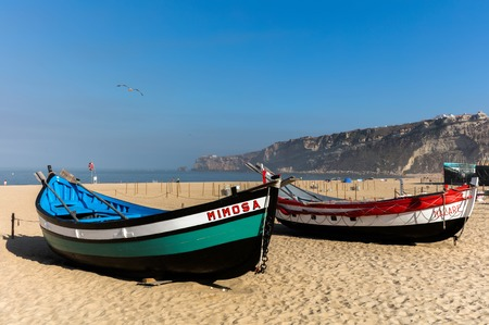 Praia da Nazare beach in Nazare,  Portugal.  Historic examples of the colorful fishing boats used by the local fishermen not so long ago.