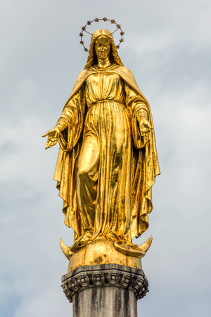 Gilded statue of Maria Immaculata on a sphere with snake and a crescent moon, sculpted by Anton Dominik Ritter von Fernkorn in 1870, placed on top of a column near Zagreb Cathedral in Zagreb, Croatia