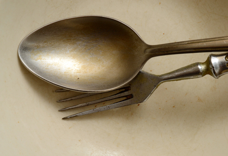 Poorly washed spoon and fork on the plate Stock Photo
