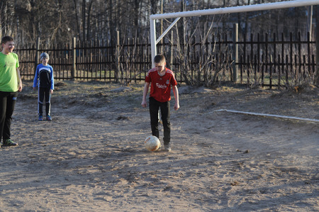schoolyard: KOVROV, RUSSIA - APRIL 12, 2015: Teenagers playing soccer in the schoolyard