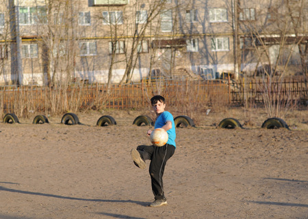 schoolyard: KOVROV, RUSSIA - APRIL 12, 2015: Teenager playing soccer in the schoolyard