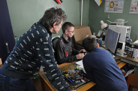 computer club: KOVROV, RUSSIA - April 18, 2015: Pupil of the childrens club Atlas flies on a computer flight simulator under the controlled a mentor