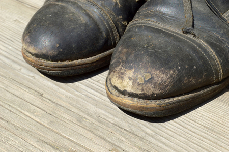 Old shoes on a wooden surface. Close-up