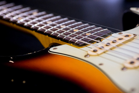 detail of vintage electric guitar neck and body on dark background Stock Photo