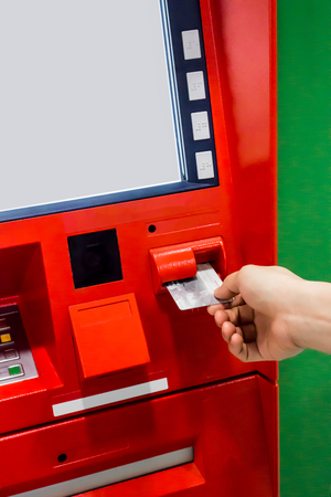 deposit slip: Hand of a woman with a credit card, using an ATM. Woman using an atm machine with her credit card.