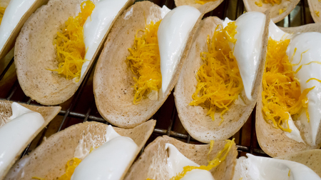 Thai traditional dessert called Ka Nhom Beuang,Thai crispy crepes filled with sweetened coconut cream and sweet egg floss Stock Photo