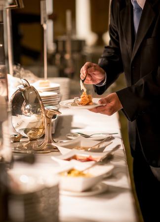Businessman hands taking food in buffet line indoor in luxury hotel Foto de archivo
