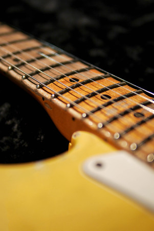 detail of vintage electric guitar scallop fingerboard on dark background. Selective focus.