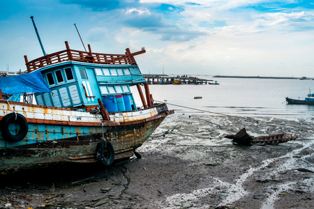 muddy: Vivid blue fishing boat tied up at low tide