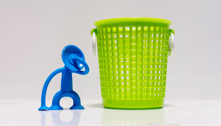 stretchy: Blue stretchy figure holding hand on face by bright green plastic basket Stock Photo