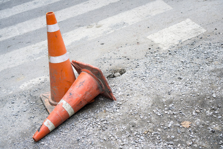 Two orange traffic cones on damage concrete road, one standing and the other one falling by crosswalk Stock Photo