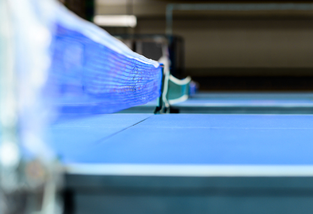 analogy: The Obstacles of Success. Steps of life. Table Tennis Net as Universal Metaphor. Blue net and table tennis with a shallow depth of field. Stock Photo