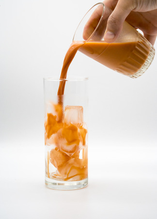pouring Thai Milk Tea into a glass with ice isolated on white background Stock Photo