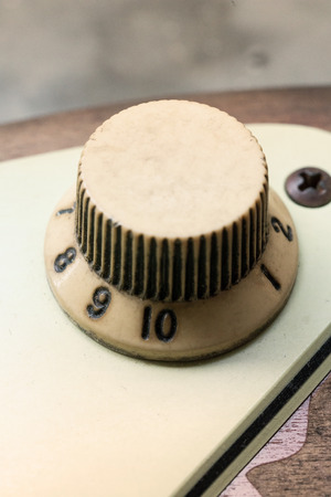 rusts: detail of vintage electric guitar knob on the concrete background. Vintage filter effect.