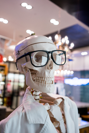 Skull head wearing eyeglasses and white scientific lab coat. Educational material for display against blurred background.