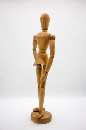 Wooden figure isolated on white background. Dummy in fashionable posing concept.