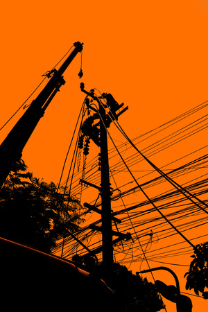 Silhouette of electricity installation and electrical maintenance services on aerial and bucket truck equipment for high reach. High-risk occupation.