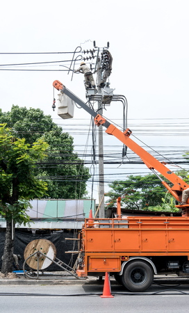 Electricity installation and electrical maintenance services on aerial and bucket truck equipment for high reach. High-risk occupation. Stock Photo
