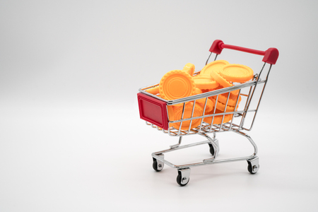 shopping cart filled with yellow coins. Symbolic image isolated on white background for money saving and expense with financial crisis concept.