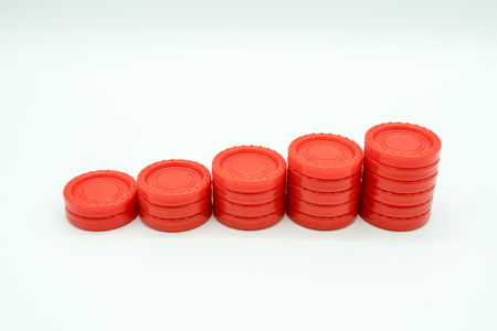 Row of coin rising stacks isolated on white background for money saving plan or financial growth concept. Stacks of red plastic coin shape from table game. Symbolic image Stock Photo